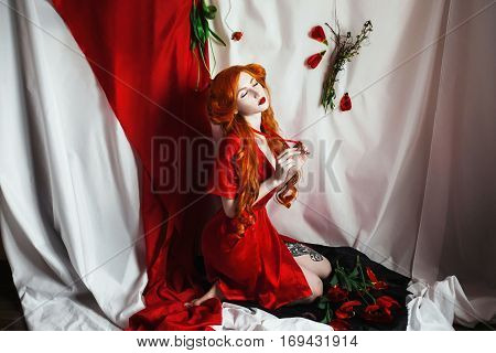 Red-haired sexy girl pin-up style on a white background. Retro lady ties a scarlet ribbon around his neck. Styling by fifties. Tulips in the background. Long-haired woman in a revealing red robe.