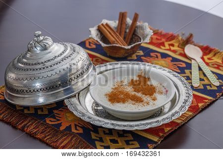 Rice pudding (sutlac) with cinnamon and wooden spoons.