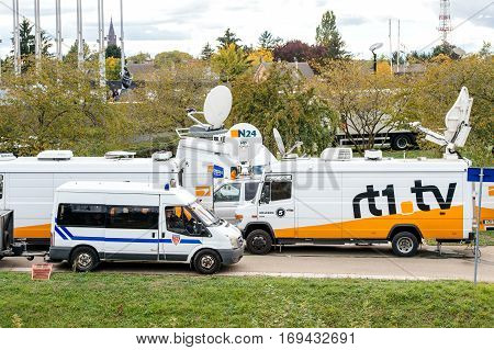 STRASBOURG FRANCE - OCT 7 2015: Tv Television Trucks with multiple Satellite parabolic antennas and fiber optic cables going inside reporting live the official French president visit to the European PArliament in Strasbourg France
