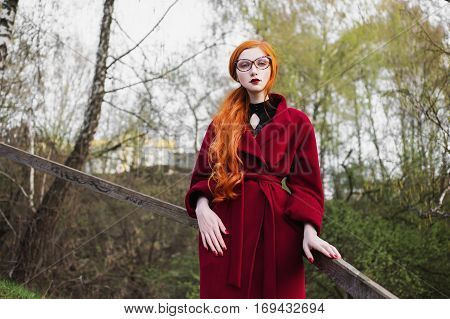 Pretty red-haired girl in a burgundy coat on the stairs. Spring Glamour portrait in retro style. Styling by fifties. Woman with long orange hair. Cat's-eye glasses.