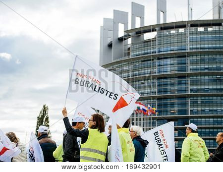 STRASBOURG FRANCE - OCT 7 2015: Rear view of tobacconists buralistes people protesting in front of the European Parliament building with flags placards while President Francois Hollande is entering the Parliament gates Confederation des buralistes