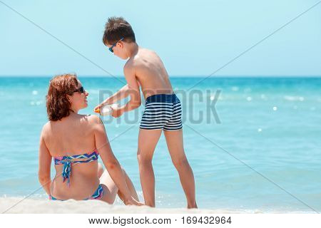 Son applying sunblock cream on his mother shoulder during summer vacation