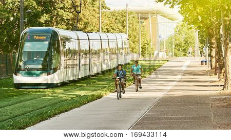 STRASBOURG FRANCE - AUG 20 2015: Two young boys riding fast ther bike to catch up the tramway on a sunny summer day in Strasbourg France at the station of European Court of Human Rights
