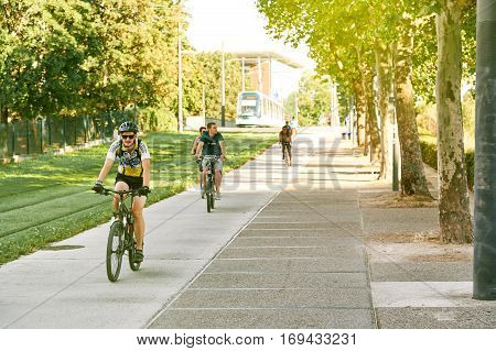 Group Of Young Sportive Boy Riding Bike On Sunny Day