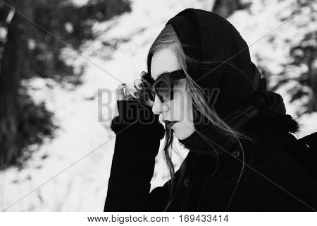 redhead stylish girl with pale skin blue eyes and burgundy red lips with a shawl on her head in a black coat on a background of a winter forest the woman with black sunglasses portrait profile