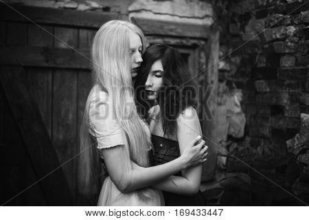 two women a girl with curly red hair and a woman with long straight white hair blonde people with pale skin and blue eyes style fashion friendship love between women