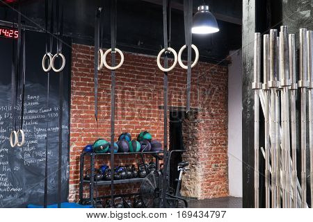 Contemporary interior of a cross-fit gym red brick wall with sport equipment