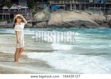 Woman in white dress walking on the beach  during summer vacation, Koh Phangan island, Thailand, Asia