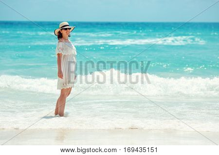Woman in white dress walking on the beach during summer vacation