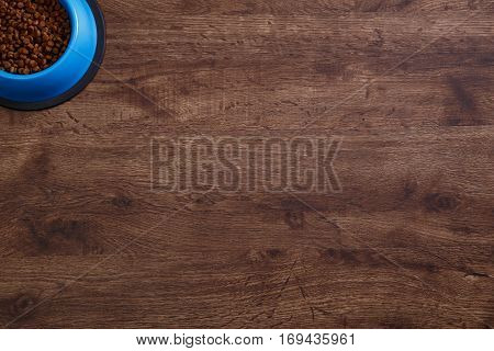 Bowl of dry kibble dog food. Healthy pets feed. Blue plate on wooden rustic background.