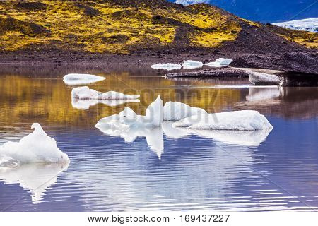 Summer in Iceland. The cold lake with splinters of ice floes formed by thawed snow of glacier Vatnajokull. The concept of extreme northern tourism