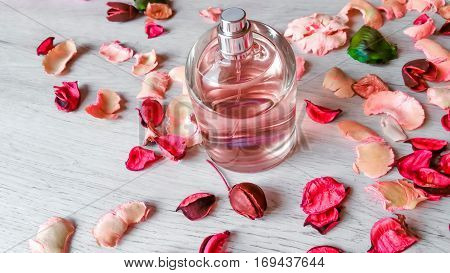 Perfume bottle with a delicate pink fragrance and rose petals on wooden background