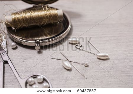 Reel gold thread on a wooden table. Pearls needles hooks bra Accessories. Tools for needlework. Workplace seamstress. Vintage