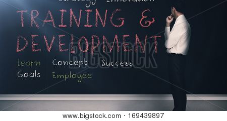Businessman looking at training and development terms written on a blackboard 3d