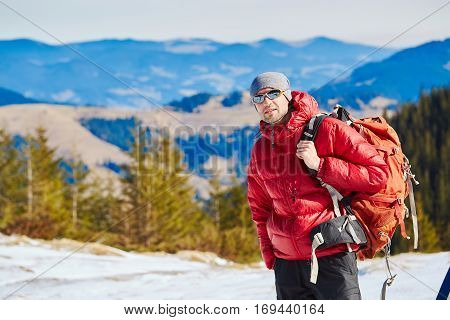 hiker in red down jacket with backpack near the tent in the Carpathians mountains at winter
