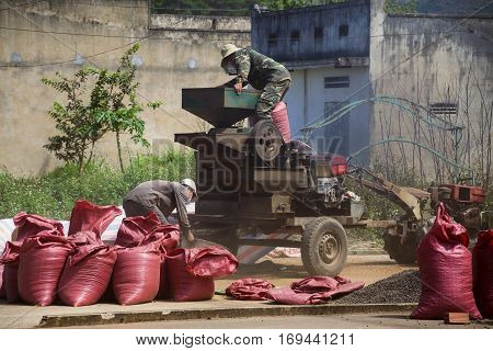 Nam Ban, Vietnam - February 11: Men Working On Coffee Beans Sorting Machine On Street On February 11