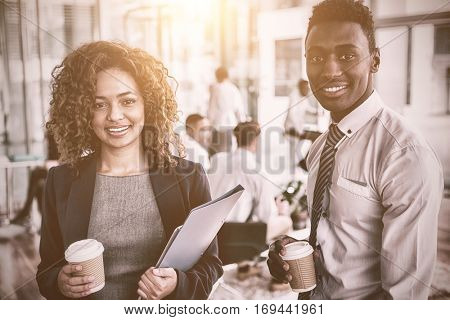 Portrait of smiling business colleagues holding disposable coffee cup in office