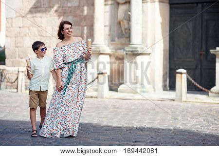 Young mother and her son walking outdoors in city, Riga, Latvia