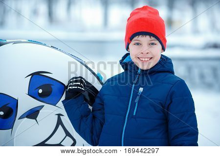 Cute little boy with snow tube playing outdoors on beautiful winter snowy day