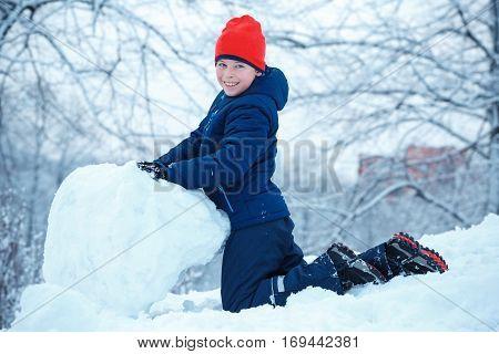 Cute little boy making a snowman on beautiful winter snowy day