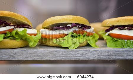 hamburger tris with salad cheese and tomato on the rock in a showcase ready to eat