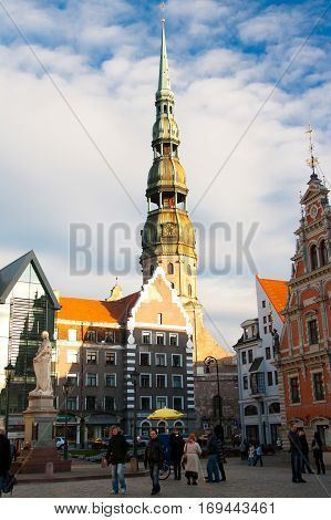 Old town square in the center of Riga Latvia. Tourist attractions House of Blackheads and St Peters church.
