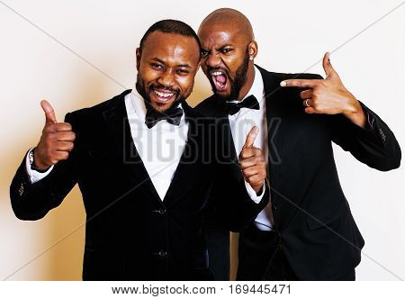 two afro-american businessmen in black suits emotional posing, gesturing, smiling. wearing bow-ties close up real friends
