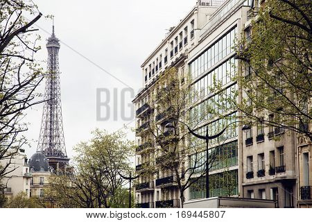 french paris street with Eiffel Tower in perspective trought trees, post card view