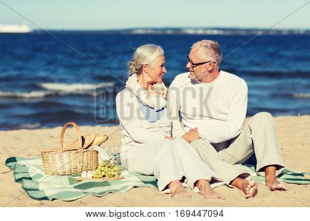 family, age, holidays, leisure and people concept - happy senior couple with picnic basket sitting on blanket on summer beach