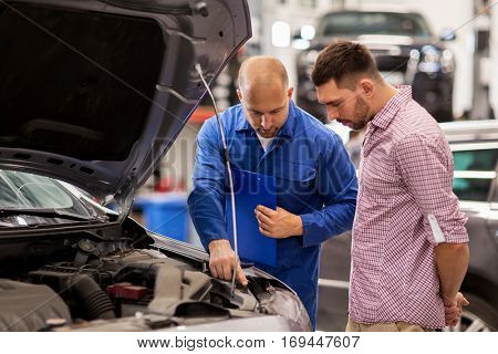 auto service, repair, maintenance and people concept - mechanic with clipboard and man or owner looking at broken car engine at shop