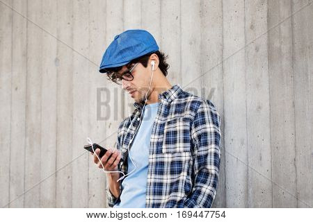 people, music, technology, leisure and lifestyle - young hipster man with earphones and smartphone listening to music