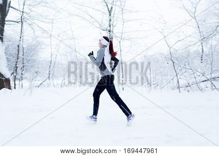 Athlete running in winter woods