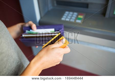 finance, money, bank and people concept - close up of hands with cash and credit card at atm machine