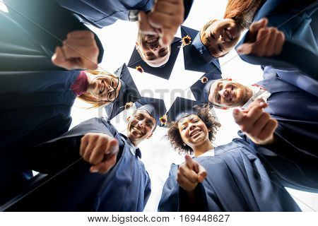 education, graduation and people concept - group of happy international students in mortar boards and bachelor gowns standing in circle and pointing finger at you
