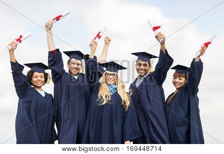 education, graduation and people concept - group of happy international students in mortar boards and bachelor gowns waving diplomas celebrating success