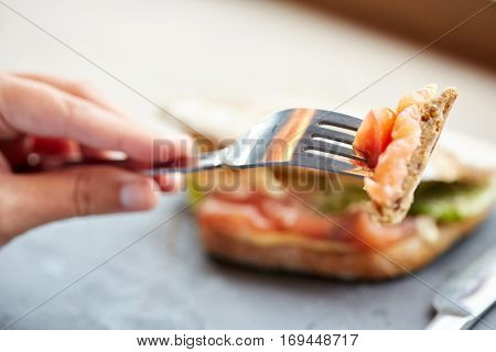 food, dinner and people concept - woman eating salmon panini sandwich with tomatoes and cheese at restaurant