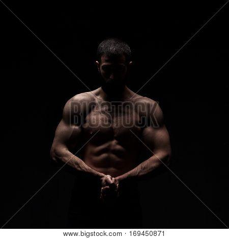 studio portrait of athlete bodybuilder man isolated over black background