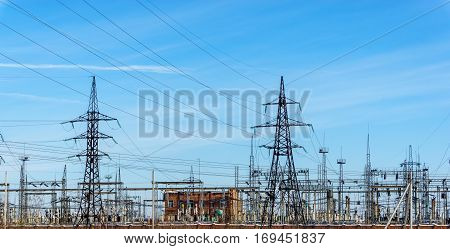 high voltage power lines at blue sky. electricity distribution station. high voltage electric transmission towers.