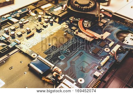 Disassembled laptop. Printed Circuit Board with many electrical components. Close up image. Technology and hardware electronic concept.