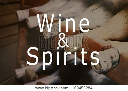Text WINE AND SPIRITS on background. Rack with old and dusty wine bottles