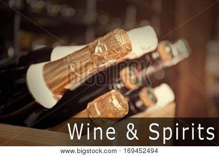 Bottles of different wine in wooden crate, closeup. Text WINE AND SPIRITS on background