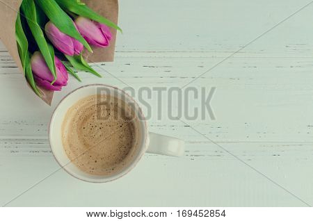 Cup of coffee with bouquet of pink tulips on white shabby chic background. Valentines Mothers Womens Day morning concept. Valentine's day breakfast. Top view. Copy space.