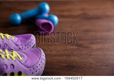 Fitness gym equipment. Sneakers, dumbbells with towel. Workout footwear. Sport trainers on grunge rustic wood background.