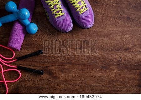 Fitness gym equipment. Sneakers, dumbbells with towel and skipping rope. Workout footwear. Sport trainers on grunge rustic wood background.