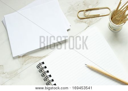 Overhead flat lay styled desk top with white stationary, open notebook, pencil and paper clips
