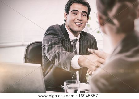 Smiling manager interviewing a female applicant in his office