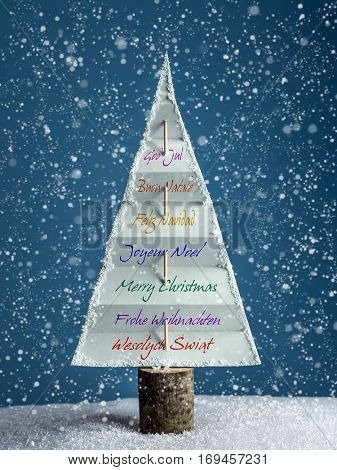 Paper christmas tree with International seasonal greetings over dark blue background with snowing effect