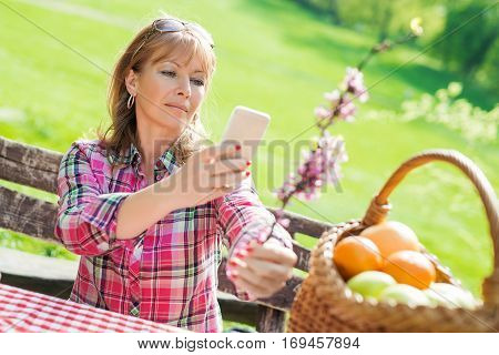 Beautiful mature woman in the park using a smart phone.