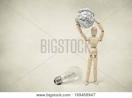 Wood Figure Mannequin carrying crumpled paper ball instead of an incandescent light bulb / Selecting a stupid chioce