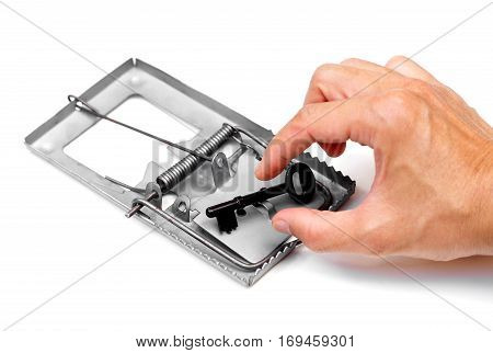 Hand of a businessman trying to pick up a key from a mouse trap / Success trap concept